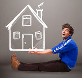 Young boy holding a huge drawn house Stock Image