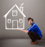 Young boy holding a huge drawn house Stock Photos