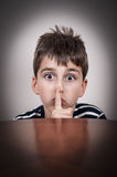 Young boy holding a index finger on his lips Royalty Free Stock Image