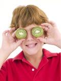 Young boy holding kiwi halves over eyes Royalty Free Stock Photography