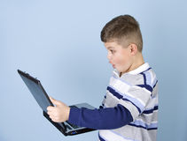 Young boy holding a laptop shocked expression. Young boy holding a laptop computer with a surprised, shocked look on his face. Blue background Stock Photo