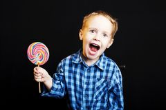 Young boy holding lollipop on black background stock image