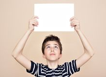 Young boy holding blank white board. Young boy holding and looking from below at blank white paper Royalty Free Stock Photography
