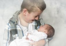 Young boy holding a new born baby boy Royalty Free Stock Photo