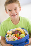 Young Boy Holding Packed Lunch In Living Room Royalty Free Stock Photo
