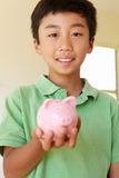 Young boy holding piggybank Stock Images