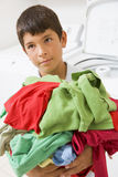 Young Boy Holding A Pile Of Laundry Royalty Free Stock Image