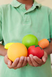 Young boy holding plastic fruit and vegetables Stock Photo