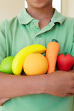 Young boy holding plastic fruit and vegetables Royalty Free Stock Images