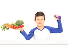 Young boy holding plate full of vegetables and dumbbell. Isolated on white background royalty free stock images