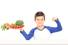 Young boy holding plate full of vegetables and showing muscle. Isolated on white background Stock Photos