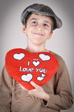 Young boy holding a plush red heart. Cute young boy with newsboy cap holding a plush red heart with I love you message on Valentine's day Stock Photography