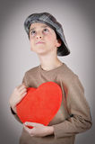 Young boy holding a plush red heart. Cute young boy with newsboy cap holding a plush red heart and looking up on Valentine's day Stock Photos