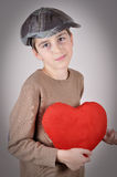 Young boy holding a plush red heart. Cute young boy with newsboy cap holding a plush red heart on Valentine's day Stock Photos