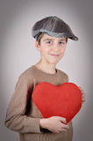 Young boy holding a plush red heart. Cute young boy with newsboy cap holding a plush red heart on Valentine's day Stock Images