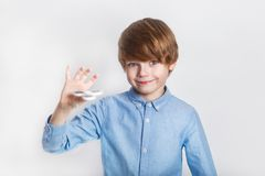 Young boy holding popular fidget spinner toy - close up portrait. Happy smiling child playing with Spinner. Young boy holding popular white fidget spinner toy stock image
