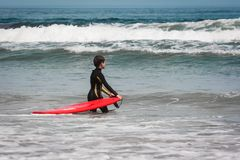 Young boy with a red surf waiting for a wave. Famara beach, Lanzarote, Canary Islands, Spain. Young boy holding a red surf waiting for a wave. Famara beach Royalty Free Stock Images
