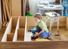 Young boy holding screwdriver while sitting on floor at unfinish Stock Photography