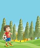 A young boy holding a soccer ball near the pine trees Stock Photo