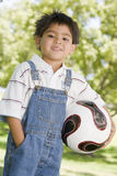 Young boy holding soccer ball outdoors smiling Stock Image