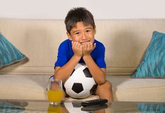 Young boy holding soccer ball watching excited and nervous football game on television biting fingernails sitting at living sofa c. Lifestyle portrait at home of royalty free stock image