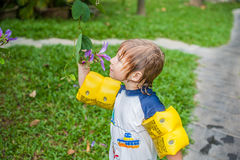 Young boy holding a tropical stem in the garden looking and smelling the flower head.  Royalty Free Stock Photos
