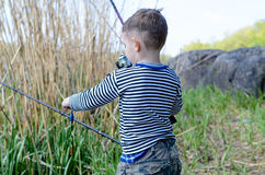 Young boy holding up his fishing rod and reel Royalty Free Stock Photography