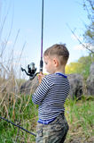 Young boy holding up his fishing rod and reel Stock Photography