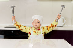 Young boy holding up kitchen tools Stock Photography