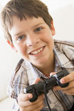 Young boy holding video game controller. Smiling Stock Photos