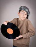 Young boy holding a vinyl record. Surprised and amazed cute young boy wearing a brown sweater and tartan newsboy cap holding and showing a vinyl record.  on gray Royalty Free Stock Photography