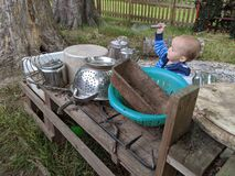 Young boy holding a whisk and playing in a mud kitchen