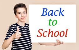 Young boy holding white board with back to school message. Young boy with thumb up holding white board with back to school message stock photos
