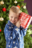 Young Boy Holding Wrapped Present In Front Of Tree Stock Photo