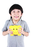 Young boy holding yellow piggy bank Royalty Free Stock Images