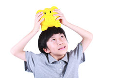 Young boy holding yellow piggy bank Stock Images