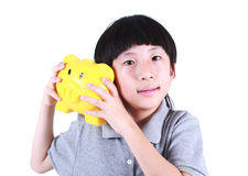 Young boy holding yellow piggy bank Royalty Free Stock Image