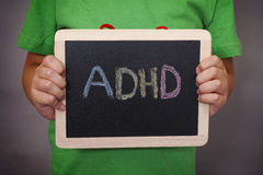 Young boy holds ADHD text written on blackboard. ADHD is Attention deficit hyperactivity disorder. Close up Royalty Free Stock Photos