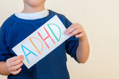 Young boy holds ADHD text Royalty Free Stock Photo