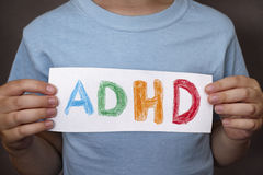 Young boy holds ADHD text written on sheet of paper Stock Photo