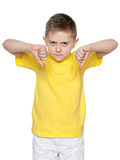 Young boy holds his thumbs down stock photography