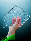 Young boy holds slice of ice floe in cold hand. Stock Photos