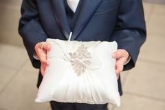 A close up view of a ring bearer holding a bridal wedding pillow decorated with sequins and the bride`s ring. stock photos