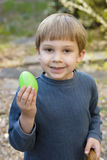 Young boy holds up easter egg. A young boy wearing a blue sweater holds a green egg Stock Photos