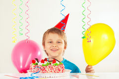 Young boy in holiday cap with festive cake and balloons Royalty Free Stock Photography