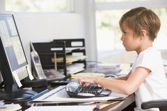 Young boy in home office with computer Royalty Free Stock Photos