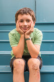 Young boy on home steps with scrapped knees. 11 year old boy in green on blue steps with scrapped knees and band aids Stock Photos