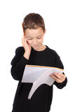 Young boy with homework. Young eight year old boy holding head due to a headache from feeling overwhelmed by school homework Stock Photo