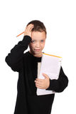 Young boy with homework headache. Young eight year old boy holding head due to a headache from feeling overwhelmed by grade school homework Royalty Free Stock Images