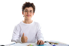 Young boy on homework smiling and showing success gesture on bla Stock Images